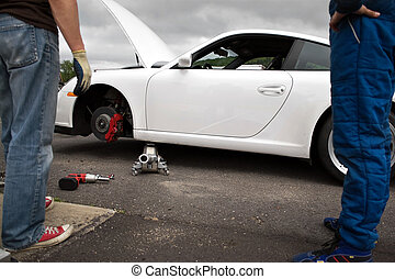 Auto Racing Pit Crew - Working on the brakes and wheel...