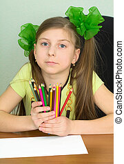 Girl with color pencils in hands and a sheet of paper