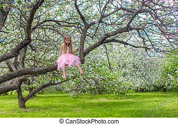 Little adorable girl on blossoming apple tree - Little...