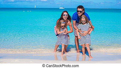 Happy family of four on beach vacation - Family of four on...