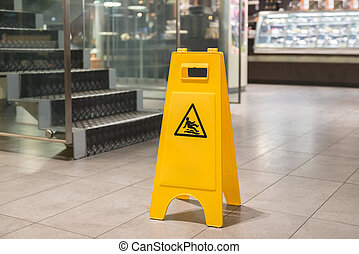 Yellow sign alerts for wet floor - Yellow sign that alerts...
