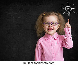 Happy kid girl in glasses with bright idea standing near...