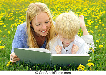Happy Mother and Child Reading Book Outside in Meadow - a...
