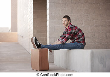 Lanky Young Man Waiting with Feet Propped on Suitcase