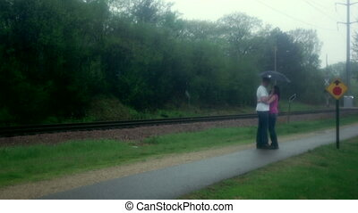 Couple kissing in rain - Young couple man and woman, kissing...