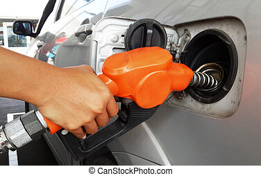 Woman hand refilling gas to car with fuel on a filling...