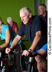 Spinning class - Senior man concentrating hard while in...