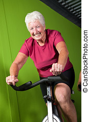 Senior lady spinning - Active senior woman on spinning bike...