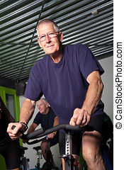 Senior cycling group - Elderly man on spinning bike in the...