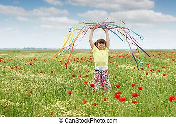 beautiful little girl waving with colorful ribbons on meadow