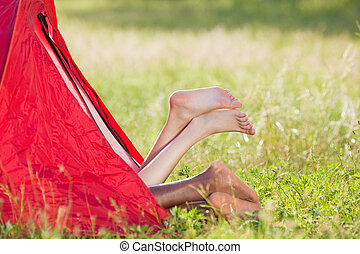 couple in tent - young multiethnic couple lying in tent with...