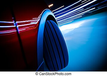 Night Ride Blurs. Car Front Wheel on the Road Curve Closeup...