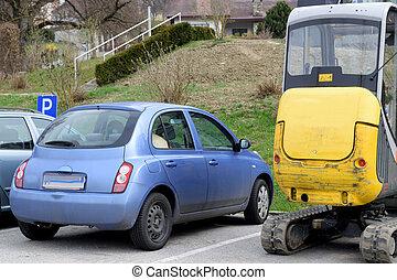 Bagger neben Autos - Bagger parkt neben Autos