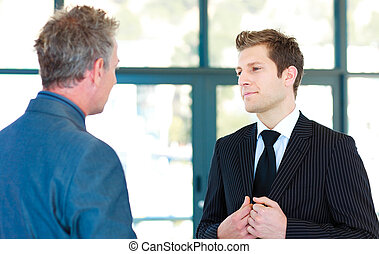Young businessman talking to a senior manager in an office