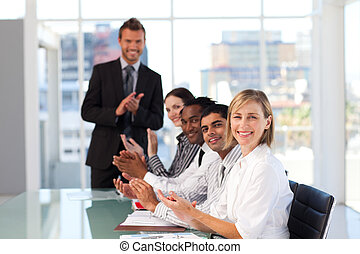 Happy manager clapping in a presentation with all her team