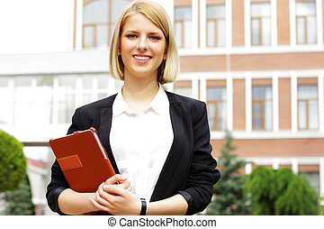 Portrait of a young smiling woman holding tablet computer outdoors
