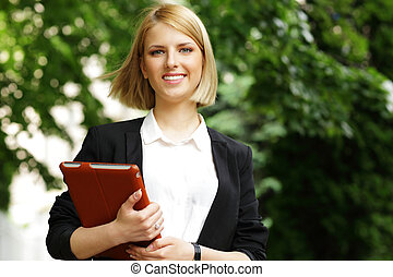 Portrait of a young smiling woman in park with tablet...