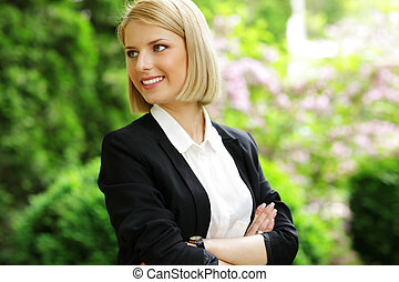 Portrait of a happy woman with arms folded looking away in...