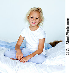 Little girl in bed smiling at the camera while her little brother is sleeping