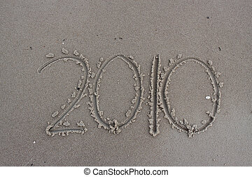 New year 2010 - Happy new year 2010 writing in sand on a...