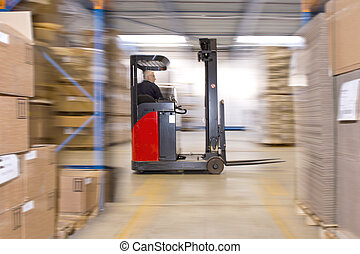 Reach truck forklift driving past an isle in a warehouse at...