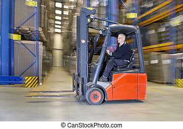 Internal logistics - Panned image Forklift driving through a...
