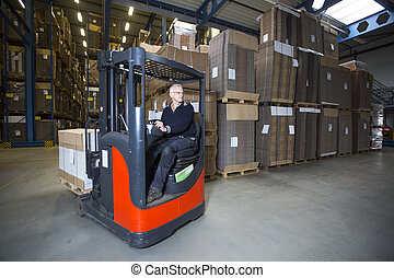 Reach truck driving around the corner in a warehouse where...