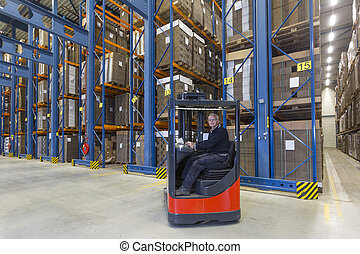 Reach Truck driver - Man driving his reachtruck into a row...