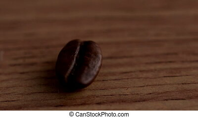 Coffee beans spinning on wooden surface in slow motion
