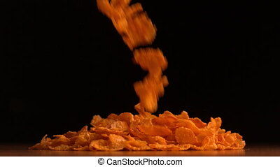 Cereal flakes pouring on black background in slow motion