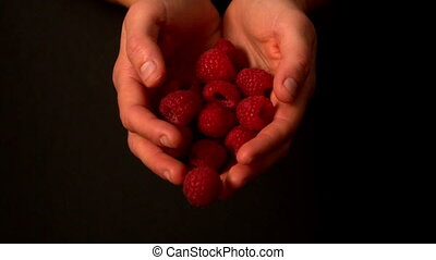 Spilling raspberries from hands in slow motion