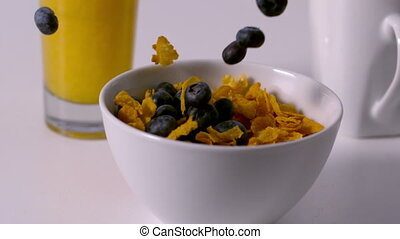Blueberries pouring into cereal bowl at breakfast table in...