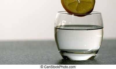Slice of orange falling into glass of water in slow motion