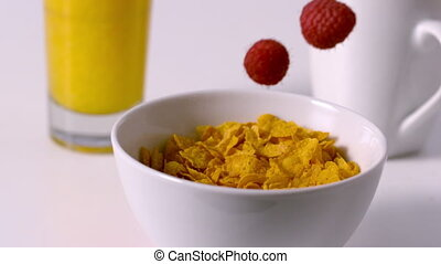 Raspberries pouring into cereal bowl at breakfast table in...