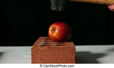 Hammer smashing apple over bricks in slow motion