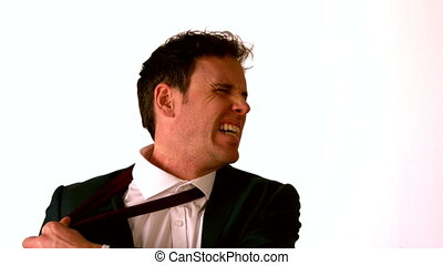 Angry businessman taking off his tie and throwing it in slow...