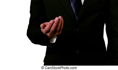 Businessman throwing and catching coins in hand in slow...