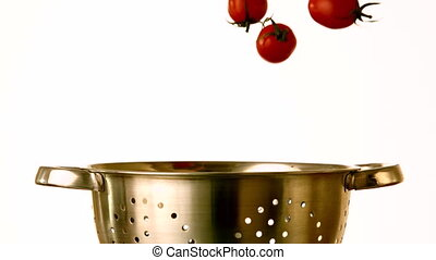 Cherry tomatoes falling into colander on white background in...