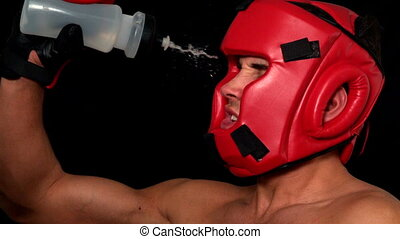 Tough boxer pouring water over his face in slow motion