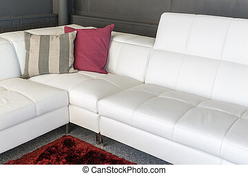 Couch with white upholstery and two pillows