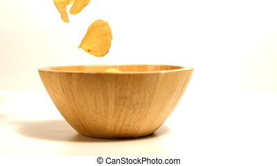 Chips falling in wooden bowl