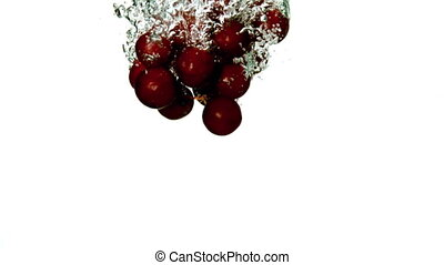 Grapes falling in water on white background in slow motion