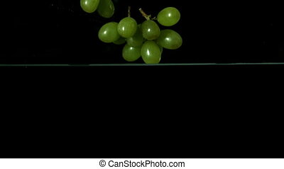 Grapes falling in water on black ba