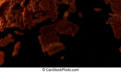 Bran flakes bouncing against black background in slow motion