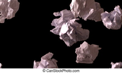 Crumpled paper falling against blac