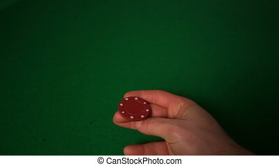 Hand flipping red casino chip
