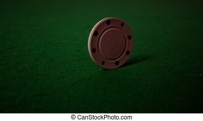 White chip spinning on casino table in slow motion