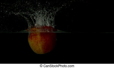 Red apple plunging into water on black background in slow...