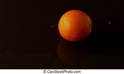 Orange dropping on wet black surface in slow motion