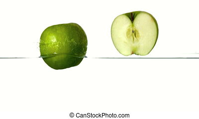 Apple halves plunging into water on white background in slow...